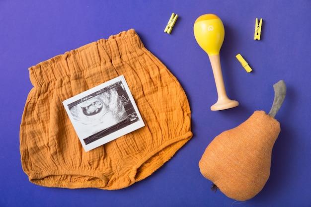Baby is kort; gevulde peer; rammelaar en gele wasknijper op blauwe achtergrond