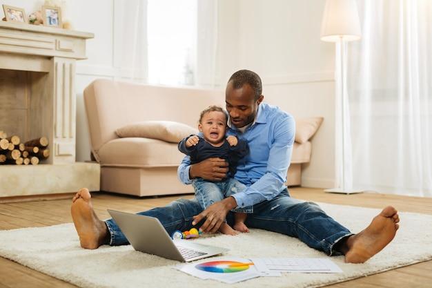 Baby jongen. zorgzame jonge afro-amerikaanse vader die een huilende baby met krullend haar vasthoudt en hem amuseert terwijl hij op de grond zit met zijn laptop en een speeltje