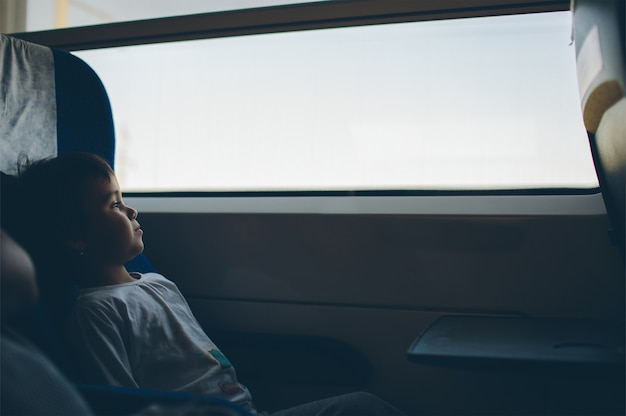 Baby kijkt uit het raam op de trein snelheid dingen