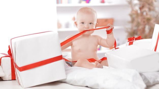 Baby kind baby peuter kind zit in cadeautjes cadeau voor feest. kerstmis nieuwjaar concept.