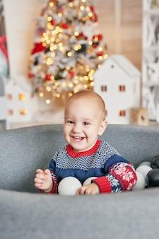 Baby kind portret met de kerstboom. kerst schattige peuter. familie vakantie concept. kinderen spelen kamer. kerst in de kinderkamer.