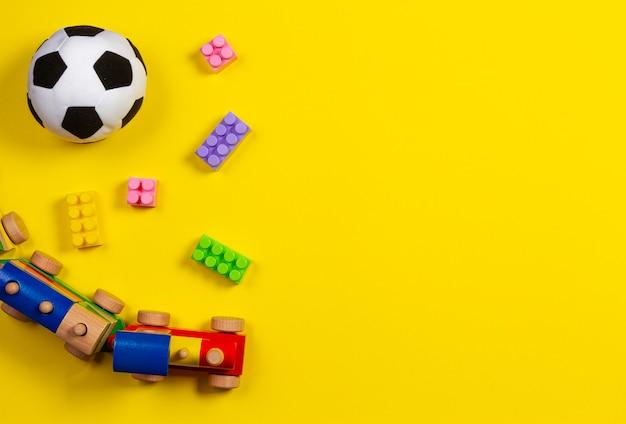 Baby kind speelgoed op gele achtergrond. bovenaanzicht