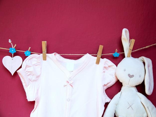 Baby kinderkleding en goederen en speelgoed hangen aan wasknijpers aan de waslijn op de muur achtergrond