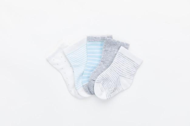 Baby kleurrijke die sokken op witte achtergrond worden geïsoleerd.