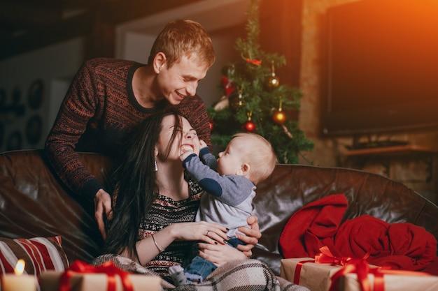 Baby knijpen en het aanraken van het gezicht van zijn moeder, terwijl de vader glimlacht