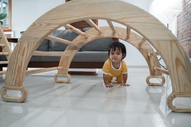 Baby kruipt langs onder de pikler klimspeelgoed in huis