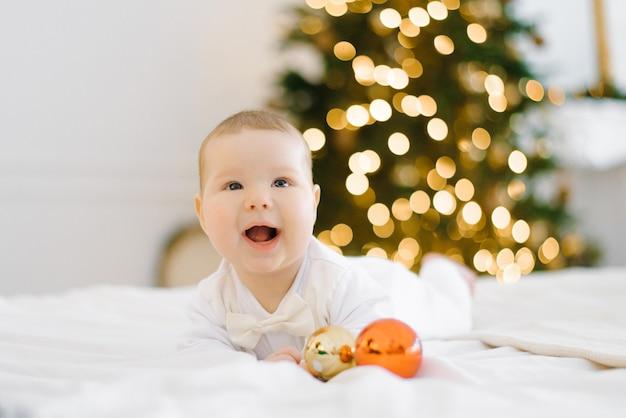 Baby lacht terwijl hij op het bed ligt op de achtergrond van kerstverlichting