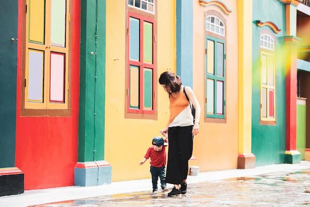 Baby leert lopen met zijn moeder in een kleurrijke straat