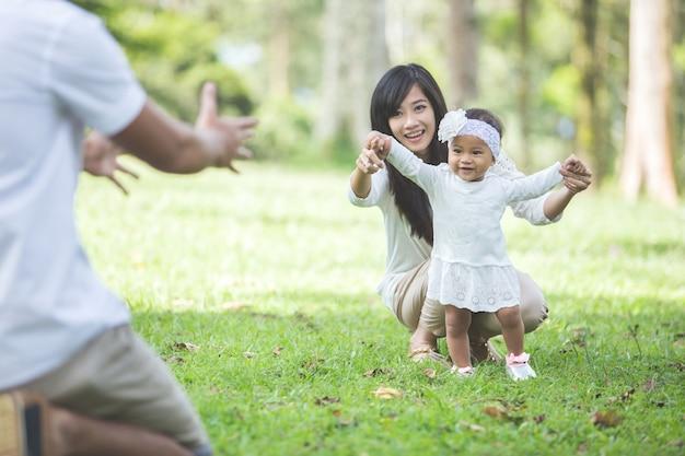 Baby leren lopen met hun ouders in het park Premium Foto