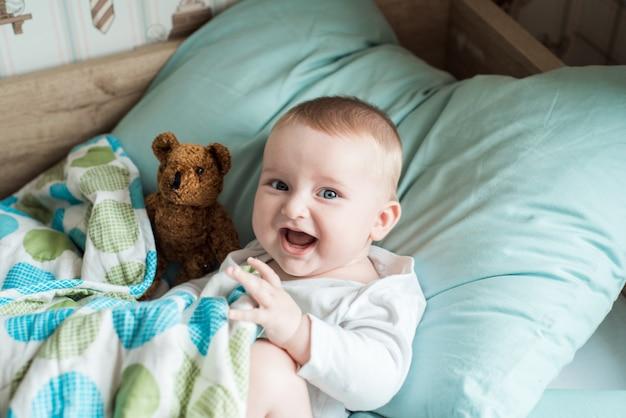 Baby liggend in bed met een pluche teddybeer
