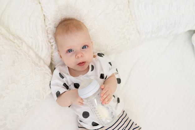Baby liggend op het bed in pyjama's en consumptiemelk uit een fles