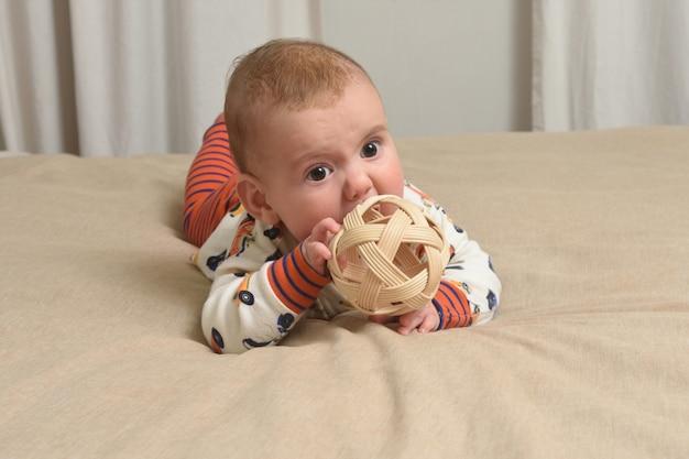 Baby liggend op het bed spelen met een stuk speelgoed, houten bal
