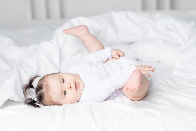 Baby liggend op het bed thuis met zijn voeten omhoog, het concept van een gelukkig liefdevol gezin en kinderen