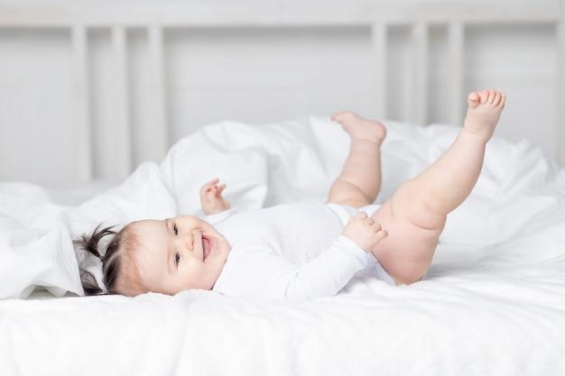 Baby liggend op het bed thuis met zijn voeten omhoog, het concept van een gelukkige liefdevolle familie en kinderen