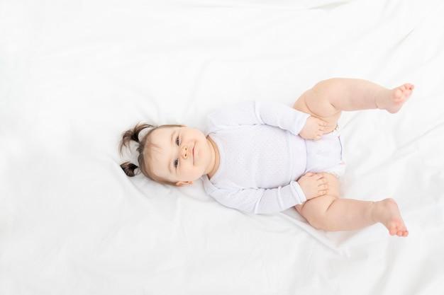 Baby liggend op het bed thuis op een wit bed, het concept van een gelukkige liefdevolle familie en kinderen