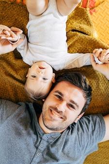Baby liggend op zijn achterhoofd hoofd tegen hoofd lachende vader met babys handen op gele deken op de vloer