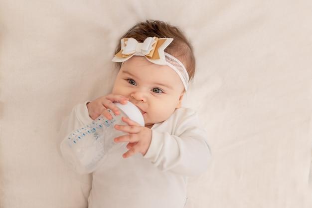 Baby ligt zes maanden in een wieg met een fles en drinkt water in een wit rompertje