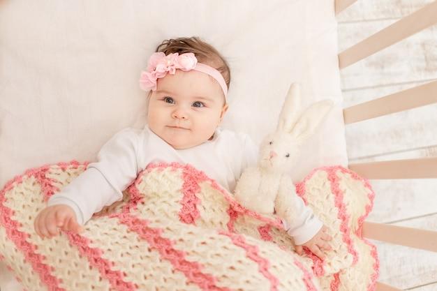 Baby ligt zes maanden in een wieg met een speelgoedhaasje onder een roze deken