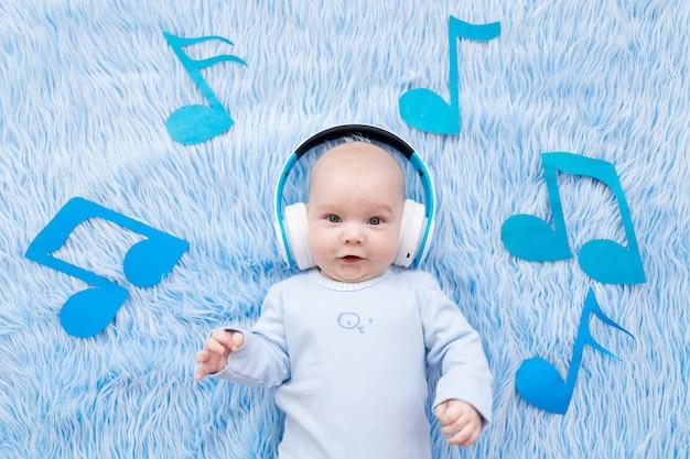 Baby luisteren naar muziek met een koptelefoon op een blauwe mat