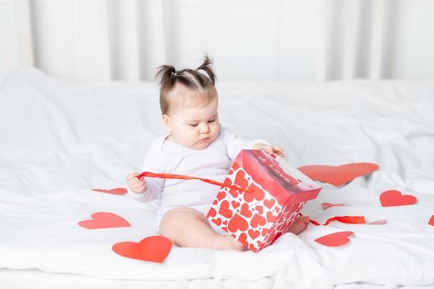 Baby maakt doos op bed thuis onder harten los, valentijnsdag concept
