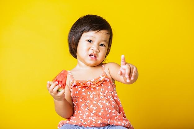 Baby meisje aantrekkelijke lach glimlach houdt gesneden watermeloen vers om te eten