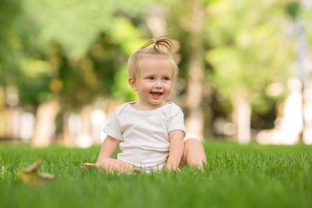 Baby meisje in een witte zandbak op het groene gras spelen piramide