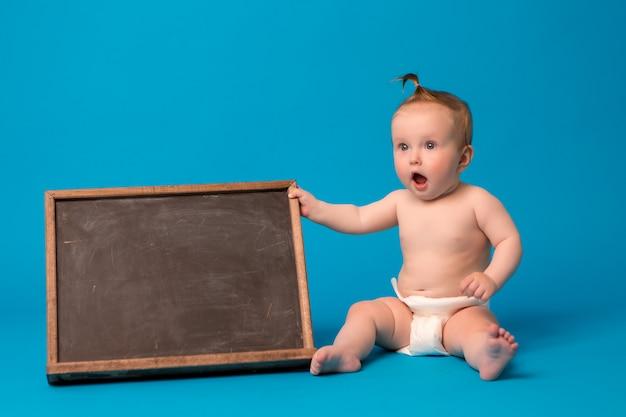 Baby meisje in luiers met een tekenbord op een blauwe achtergrond