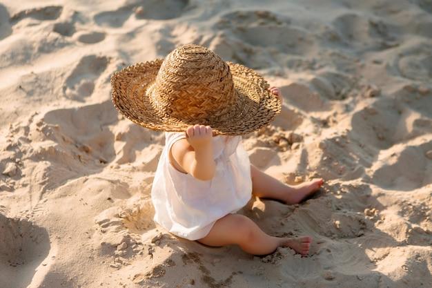 Baby meisje in witte kleren en een strooien hoed zit op het witte zand op het strand in de zomer