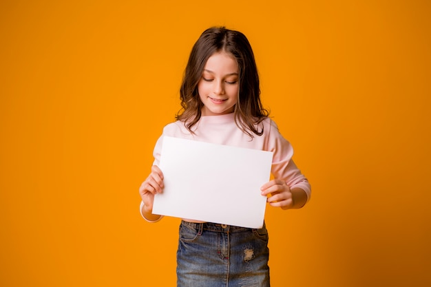Baby meisje lachend met een blanco vel op een gele achtergrond