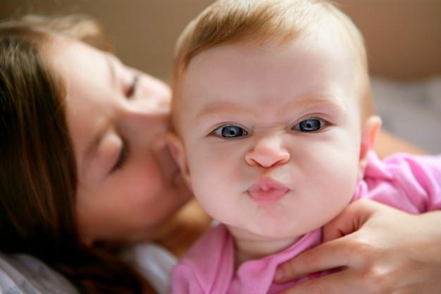 Baby meisje met grappige uitdrukking in haar gezicht gekust door haar grote zus