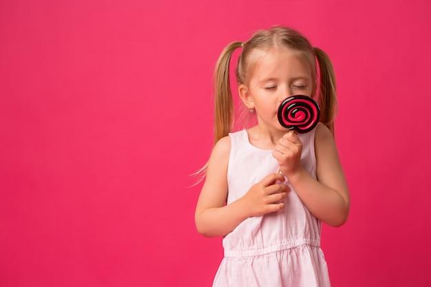 Baby meisje met lollipop op roze achtergrond