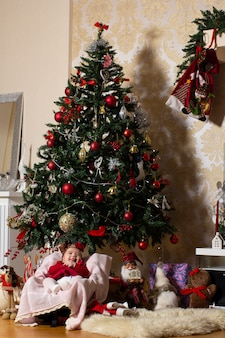 Baby meisje onder kerstboom met knuffels