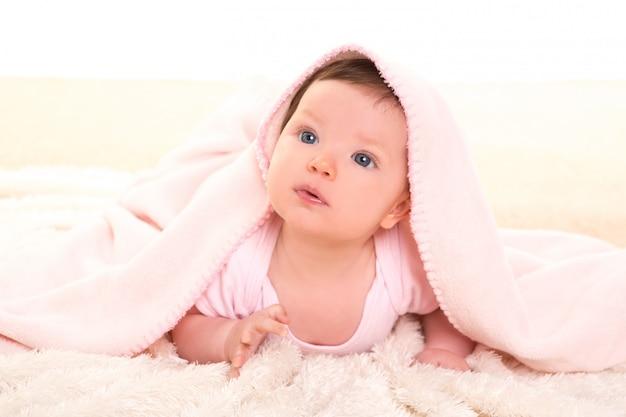 Baby meisje onder verborgen roze deken op witte vacht