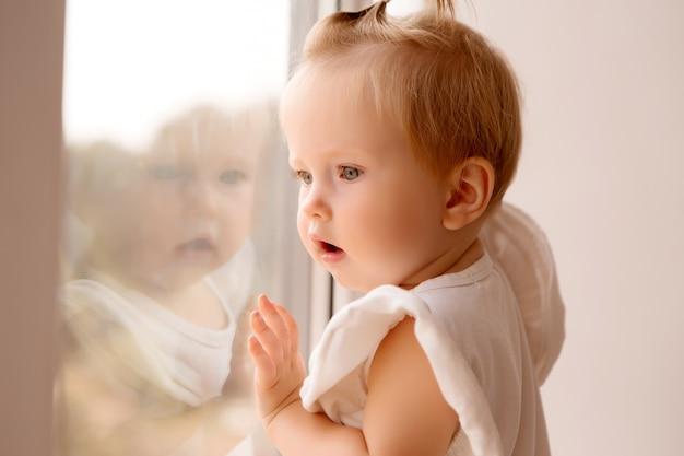 Baby meisje staat op de vensterbank en kijkt uit het raam