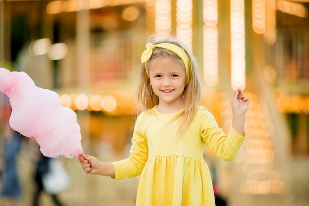 Baby meisje wandelen in het park en het eten van suikerspin