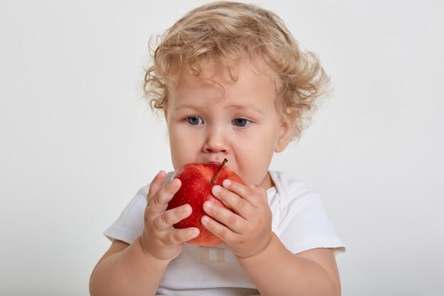 Baby met appel poseren geïsoleerd over wit