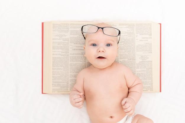 Baby met bril en een boek over een lichte achtergrond, leer- en ontwikkelingsconcept