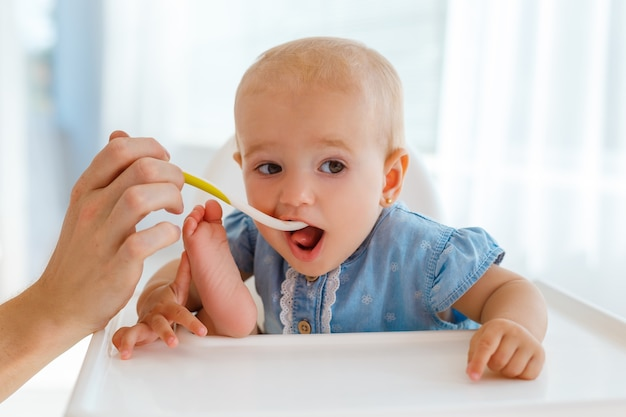 Baby met de lepel in de hand die het fruitpuree van de jonge geitjesvoeding eet. klein meisje, zittend op de voedingstafel