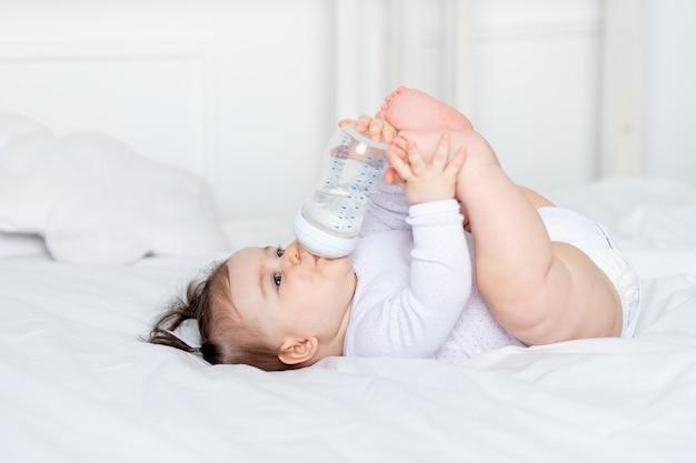 Baby met een fles op het bed thuis, babyvoeding concept