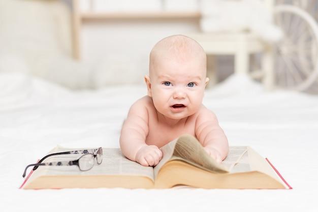Baby met een groot boek en een bril in het kinderdagverblijf, leer- en ontwikkelingsconcept