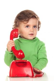 Baby met één jaar oud die met een rode telefoon speelt