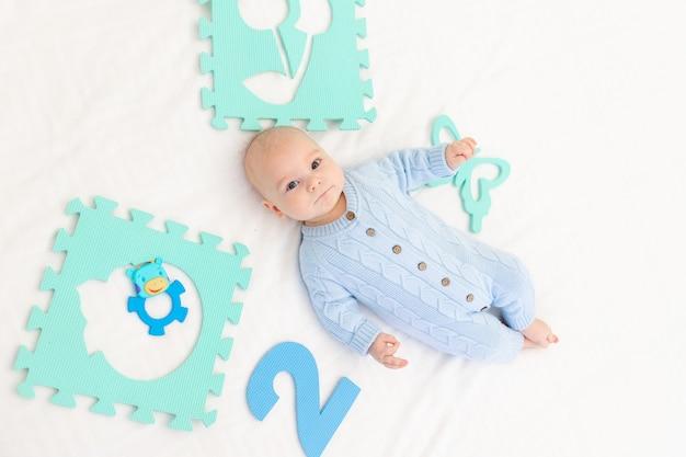 Baby met een ontwikkelingsmat op het bed. games voor kinderen. baby's activiteit