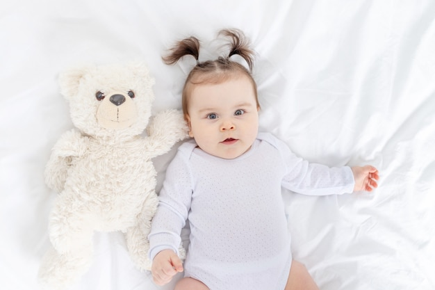 Baby met een teddybeer die thuis op het bed ligt, het concept van spelen en ontwikkeling van kinderen