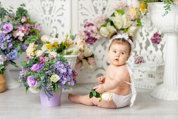 Baby met engelenvleugels onder bloemen, valentijnsdagconcept,