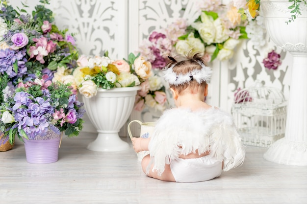 Baby met engelenvleugels tussen bloemen, valentijnsdag concept, achteraanzicht