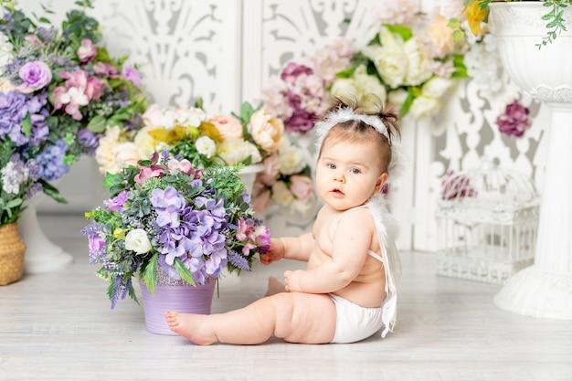 Baby met engelenvleugels tussen bloemen, valentijnsdag concept,