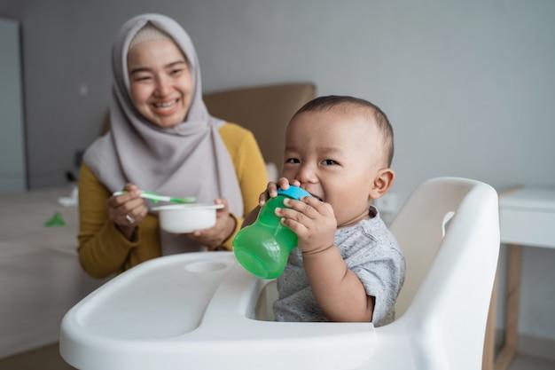 Baby met fles water zittend op een stoel