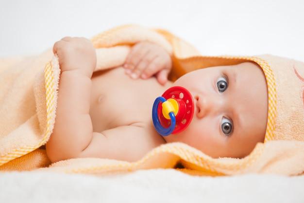 Baby met fopspeen liggend op deken.