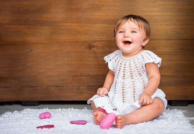 Baby met hartjes op een houten achtergrond. babysitting op tapijt met roze harten die op houten achtergrond lachen