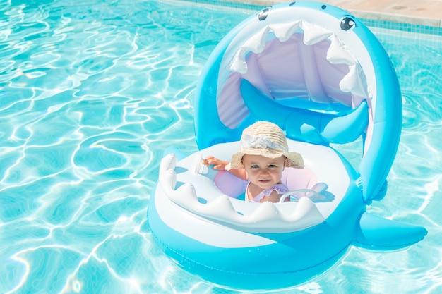 Baby met hoed op een haai-vormige vlotter in het zwembad